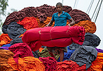 Pictured: A worker takes a well earned rest from unloading hundreds of bundles of brightly coloured cloth from a lorry.   He stretches out on the fabrics which will eventually be made into various garments and sent to local shops.<br /> <br /> The images were captured in Sirajganj in Bangladesh by photographer Abdul Momin.   Around 400 bundles are piled into the back of the large truck which is then driven to Dhaka where they are transformed into clothes and blankets.   SEE OUR COPY FOR DETAILS<br /> <br /> Please byline: Abdul Momin/Solent News<br /> <br /> © Abdul Momin/Solent News & Photo Agency<br /> UK +44 (0) 2380 458800