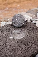 Ancient Hawaiian grindig stone replica in Nualolo Kai village, Na Pali coast, Kauai