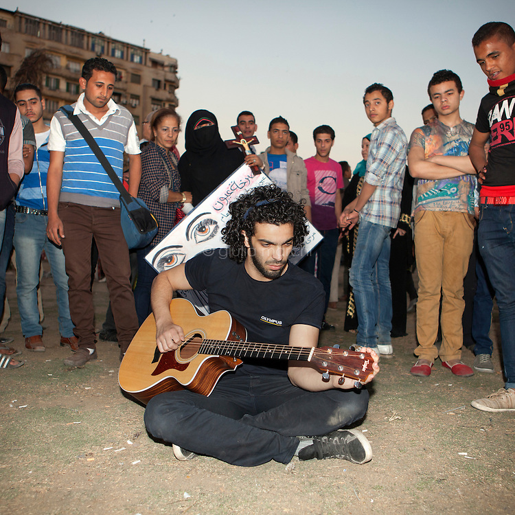 Egypt / Cairo / 5.4.2013 / Ramy Essam, Egyptian musician, poses with his guitar in Tahrir Square, in Downtown Cairo. As soon as Ramy took his guitar people in the square immediately surrounded him.  © Giulia Marchi