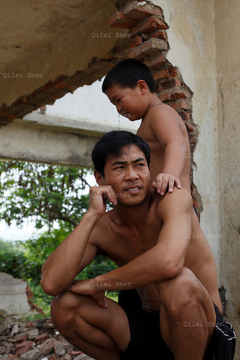 Two squatters, a man and his son, photographed at a half demolished building that serves as their home near Huzhou, China on 20 August 2009.