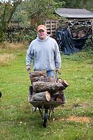 Man carrying wood in a wheelbarrow on the farm in Poland.  Zawady  Central Poland