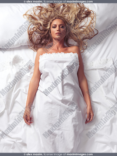 Beautiful young woman with long blond hair lying in bed covered with a sheet