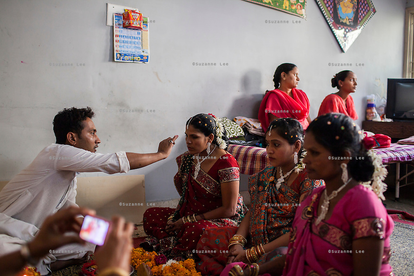 A hindu priest blesses three surrogates (Bharti Utrekar in center) who are in their 7th month of pregnancy at a baby shower organised for them in the surrogate's house in Anand, Gujarat, India on 11th December 2012. Photo by Suzanne Lee / Marie-Claire France