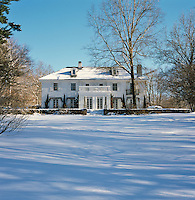 The shingle-clad front facade of the property from across the snow-covered garden