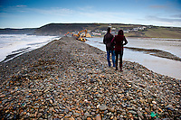 Tuesday 07 January 2014<br /> Pictured: People look on as diggers work to clear the pebbles <br /> Re: Workers try to clear stones thrown over the road by the sea at Newgale, Pembrokeshire after has been battered by the wind and High Tides over the last few days