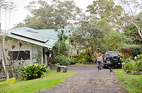 An older local Asian woman walks her dog in the driveway of her home in Pa'auilo Mauka, Big Island.