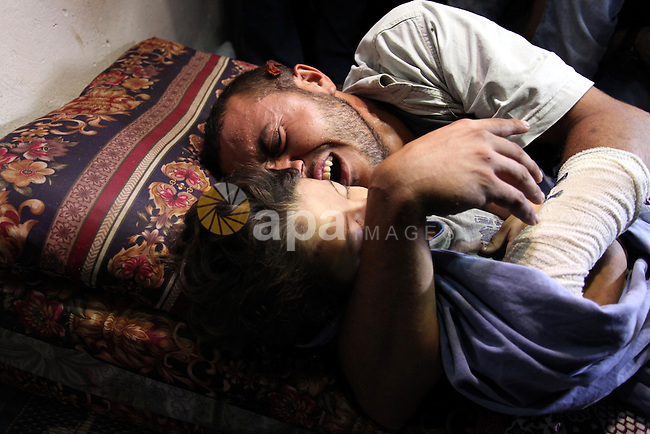 """Palestinian father Yehya Hasan mourns while holding the body of his daughter, Rahaf, during a funeral for the toddler and her pregnant mother on October 11, 2015, at the al-Nusairat refugee camp, in central Gaza Strip. A pregnant Palestinian mother and her two-year-old daughter were killed in the air strike in the Zeitun sector south of Gaza City while three others were still trapped under the ruins of a house, medical sources said. Israel said it had targeted """"two Hamas weapon manufacturing facilities"""" in response to two rocket launches at Israel the day before. Photo by Ashraf Amra"""