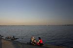 Giżycko, 2005-07-05. Para młodych ludzi siedząca na brzegu jeziora NIegocin.