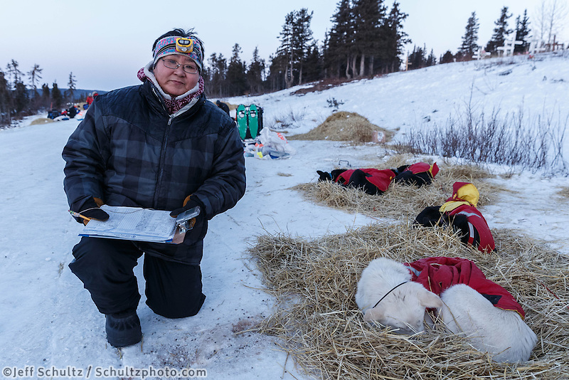Volunteer night-time checker Margaret Douglas of Koyuk checks dogs at Koyuk on Monday March 10, during the Iditarod Sled Dog Race 2014.<br /> <br /> PHOTO (c) BY JEFF SCHULTZ/IditarodPhotos.com -- REPRODUCTION PROHIBITED WITHOUT PERMISSION