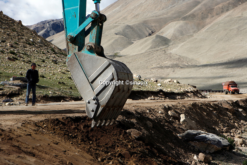 "A digger clears a road to everest base camp.<br /> China started building a controversial 67-mile ""paved highway fenced with undulating guardrails"" to Mount Qomolangma, known in the west as Mount Everest, to help facilitate next year's Olympic Games torch relay.<br /> Tibet, China<br /> July, 2007"