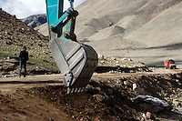 A digger clears a road to everest base camp.<br /> China started building a controversial 67-mile &quot;paved highway fenced with undulating guardrails&quot; to Mount Qomolangma, known in the west as Mount Everest, to help facilitate next year's Olympic Games torch relay.<br /> Tibet, China<br /> July, 2007