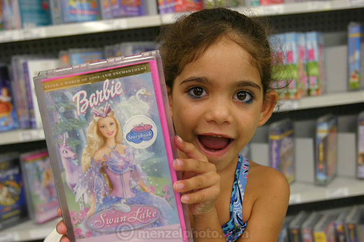 (MODEL RELEASED IMAGE). 5-year old Sinead Brown shows off the Barbie video that she wants to rent during a family grocery shopping trip near their home in Riverview, Australia. (Supporting image from the project Hungry Planet: What the World Eats.)