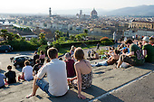 Young people on a terrace overlooking the River Arno and the landmark Duomo, Florence, Italy.