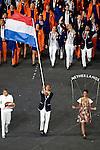 Engeland, London, 27 juli 2012.Olympische Spelen London.De openingsceremonie van de Olympische Spelen in London 2012.Dorian van Rijsselberghe draagt voor Nederland op vrijdag 27 juli in Londen namens de Nederlandse olympische ploeg de vlag bij de openingsceremonie van de Olympische Spelen