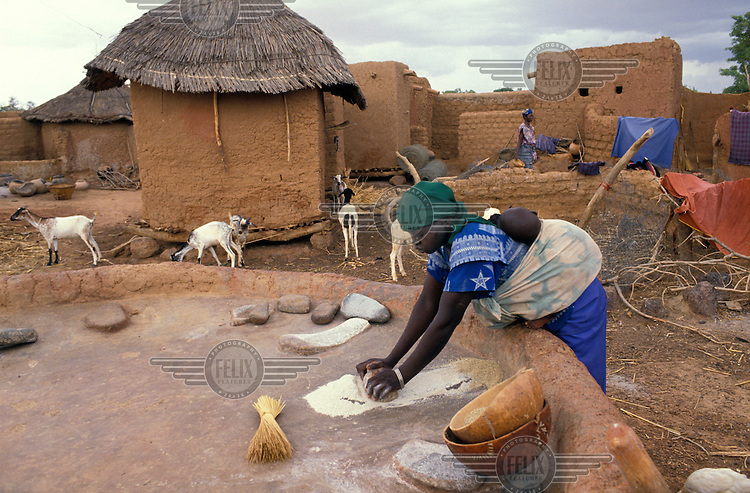 A woman grinding millet in front of a grain silo in a small village.