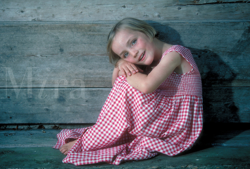 Portrait of a smiling young girl in red gingham dress, posing in contrast to weathered, gray wood. Leoni. Germany.