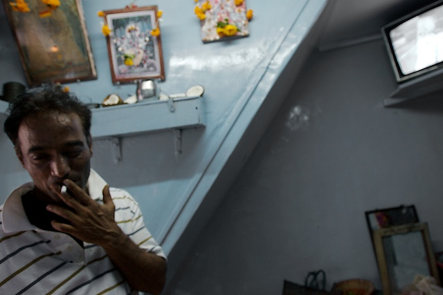 A customer, waiting for one of the women in a brothel on 14th Lane, Kamathipura. Many of the men who visit the women are drunk, on drugs, or both.