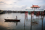 An Indonesian navigates the harbor's waters by boat, passing a dragon boat station on stilts, on Monday, April 19, 2010.