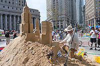 "New York, NY -  13 August 2011 A man builds sand castles in Foley Square on the second of three car-free Saturdays in August called ""Summer Streets"""