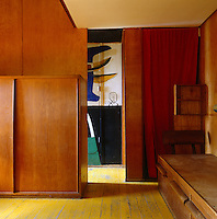 The red curtain in the corner or the room screens the toilet from the rest of the minimal one-room living space at Le Corbusier's Cabanon