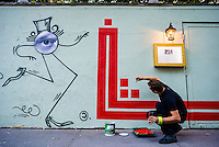 """New York, NY 18 September 2015 - French Graffiti artist L'Atlas at work on a mural. His """"abstract calligraphy"""" creats a strong contrast to the work of French graffiti artist JR whose work appears on the right."""