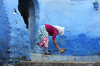 Woman sweeping the steps in a street painted blue in the medina or old town of Chefchaouen in the Rif mountains of North West Morocco. Chefchaouen was founded in 1471 by Moulay Ali Ben Moussa Ben Rashid El Alami to house the muslims expelled from Andalusia. It is famous for its blue painted houses, originated by the Jewish community, and is listed by UNESCO under the Intangible Cultural Heritage of Humanity. Picture by Manuel Cohen