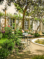 The enclosed courtyard garden is bathed in sunshine