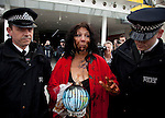 Tearful and covered in oil (chocolate syrup), Diane Wilson, a shrimp fisherwoman from an area of Louisiana affected by the 2010 Deepwater Horizon oil spill in the Gulf of Mexico, is led away by police after she gained entry to the Excel Centre in London during a BP shareholder's AGM.