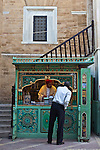 A man browses the offerings of a bookseller next to the Jemaa Zitouna (Great Mosque) deep in the Tunis Medina (Tunisia).