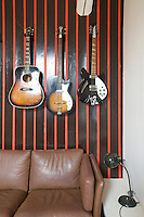 Vintage guitars are displayed on a red-and-black striped wall in the living room