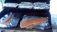 Salmon and corn cooking on grill