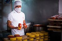 Portrait of a worker waxing cheese in the cheese factory at Hacienda Zuleta, Imbabura, Ecuador, South America