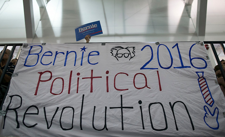 "UNITED STATES - August 16: A lone campaign sign is waived above a banner as Sen. Bernie Sanders, D-Vt., speaks at the Loras College Athletic and Wellness Center in Dubuque, Iowa, on Sunday, August 16, 2015. The ""town meeting,"" was the fourth campaign event of the day for Sanders. (Photo By Al Drago/CQ Roll Call)"