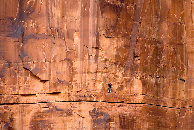 A SOLITARY ROCK CLIMBER RAPELLS DOWN A STEEP ROCK FACE IN THE MOAB, UTAH AREA
