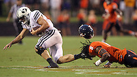 Virginia safety Anthony Harris (8) has his helmet dislodged by the foot of Brigham Young quarterback Taysom Hill (4) during the second half of the game in Charlottesville, Va. Virginia defeated Brigham Young 19-16. Photo/Andrew Shurtleff