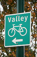 Bicyle path sign with autumn foliage in background, Vancouver, BC, Canada