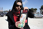 "A Palestinian activist holds News Israeli Shekels' bills marked with stickers reading ""Free Palestine"" on March 7, 2011 in the West Bank city of Ramallah, as part of a campaign aimed to peacefully express opposition to Israel's occupation. Young Palestinian activists have found a new medium to protest Israeli occupation: scrawling anti-occupation slogans on the currency they share with the Jewish state. Photo by Issam Rimawi"