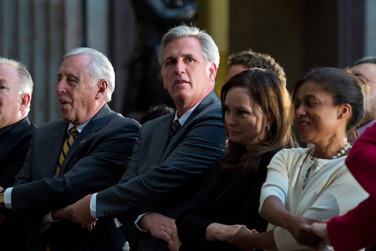 "UNITED STATES - JUNE 24: From left, Patrick Conway Chaplain of the House, House Minority Whip Steny Hoyer, D-Md., and Rep. Kevin McCarthy, R-Calif., incoming House Majority Leader, join hands to sing ""We Shall Overcome"" during a Congressional Gold Medal ceremony to mark the 50th anniversary of the Civil Rights Act of 1964, in the Capitol rotunda, June 24, 2014. (Photo By Tom Williams/CQ Roll Call)"