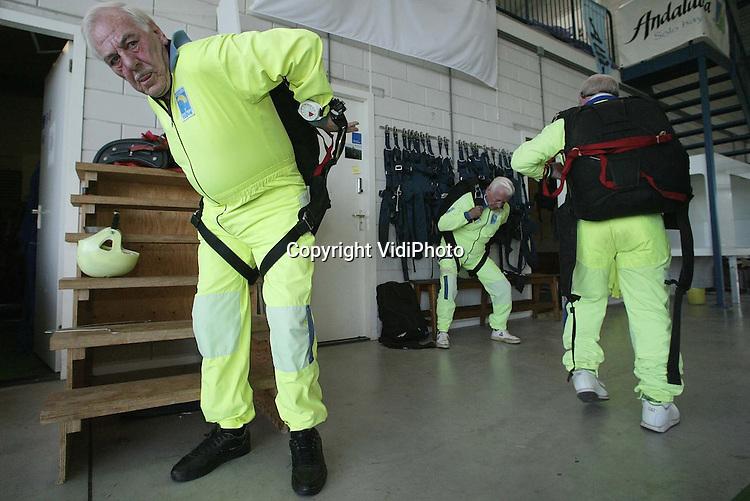 Foto: VidiPhoto. .TEUGE - Vier van de negen Engelse oorlogsveteren die zaterdag per parachute gedropt worden op de Ginkelse hei bij Ede, oefenden vrijdag op vliegveld Teuge. De leeftijd van de bejaarde para's varieert tussen de 77 en 83 jaar. Eén van de negen is blind. Drie maken er zaterdag een solosprong. De anderen springen samen met een instructeur in tandem. De veteranen hebben in 1944 meegedaan met de operatie Market Garden. De generale repetitie van vrijdag verliep vlekkeloos.