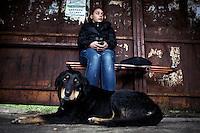 BULGARIA, Sofia, 2012/04/5..A stray dog ??is lying in front of a student waiting for the bus in the district of Lyulin in Sofia, Bulgaria..BULGARIE, Sofia, 2012/04/5..Un chien errant est allongé devant une étudiante qui attend son bus dans le  quartier de Lyulin à Sofia, Bulgarie..© Pierre Marsaut