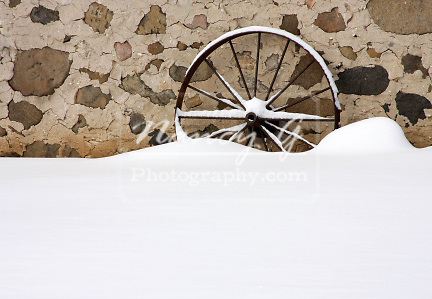 A wagon wheel leaning on a stone barn foundation in winter