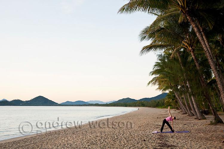 Woman doing yoga on beach at Palm Cove, Cairns, Queensland, Australia