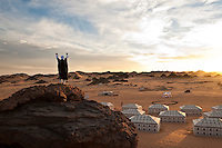 A man with his arms raised stands on top of a rock overlooking the Akakus Magic Lodge camp at sunrise