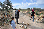 Jamal Amira with his daughters during a walk to his land in the village of Na'alin, West Bank. They pass by some leftovers of Israeli army ammunition from the anti-fence protests that regularly taking place there.