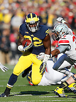 Ohio State Buckeyes linebacker Joshua Perry (37) tackles Michigan Wolverines running back De'Veon Smith (32) as he runs the ball in the third quarter of the college football game between the Ohio State Buckeyes and the Michigan Wolverines at Michigan Stadium in Ann Arbor, Michigan Saturday afternoon, November 30, 2013. The Ohio State Buckeyes defeated the Michigan Wolverines 42 - 41. (The Columbus Dispatch / Eamon Queeney)