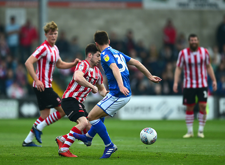 Lincoln City's Tom Pett  vies for possession with Macclesfield Town's Reece Cole<br /> <br /> Photographer Andrew Vaughan/CameraSport<br /> <br /> The EFL Sky Bet League Two - Lincoln City v Macclesfield Town - Saturday 30th March 2019 - Sincil Bank - Lincoln<br /> <br /> World Copyright © 2019 CameraSport. All rights reserved. 43 Linden Ave. Countesthorpe. Leicester. England. LE8 5PG - Tel: +44 (0) 116 277 4147 - admin@camerasport.com - www.camerasport.com