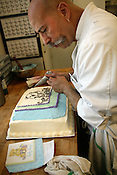 June 01, 2009. Durham, NC..Alfredo Morua Averhoff, Mad Hatter's pastry chef, draws a teddy bear from an image found on a napkin onto a cake, as per the client's request.