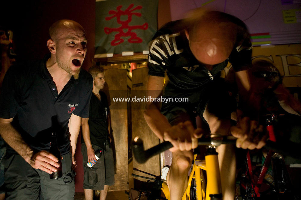 30 June 2005 - Brooklyn, NY, USA - A friend (L) encourages Gijs Derijk (R) from Utrecht in Holland, as he races in a qualifying 500m race on a stationary hometrainer known as a Goldsprint in a bar in Brooklyn, USA, June 30th 2005, one of the events of the 13th annual cycle messenger world championships. More than 700 riders from all over the world took part in the 4-day competition which carries event based on the daily work of a city bike messenger. Photo Credit: David Brabyn/Sipa Press