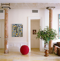 In the living rooom an outsize glass vase containing a large arrangement of greenery is placed next to a  contemporary abstract painting and a floor sculpture