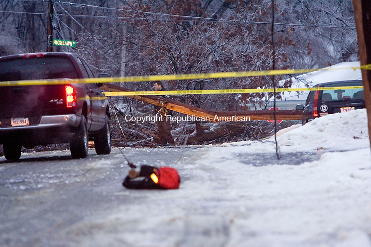 WATERBURY, CT - 07 JANUARY 2009 -010709JT02-<br /> Emergency workers investigate the scene where a woman was struck by a large tree branch as she was walking in front of 306 Mansfield Avenue on Wednesday in Waterbury. The woman sustained serious head injuries. Buckling under the weight of ice that accumulated during Wednesday's ice storm, the tree also brought a telephone pole down with it, resulting in downed power and telephone lines at the intersection of Highlawn Street.<br /> Josalee Thrift / Republican-American